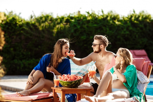 Friends smiling, eating watermelon, drinking cocktails, relaxing near swimming pool