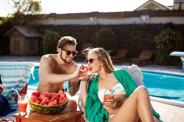 Friends smiling, eating watermelon, relaxing, lying near swimming pool