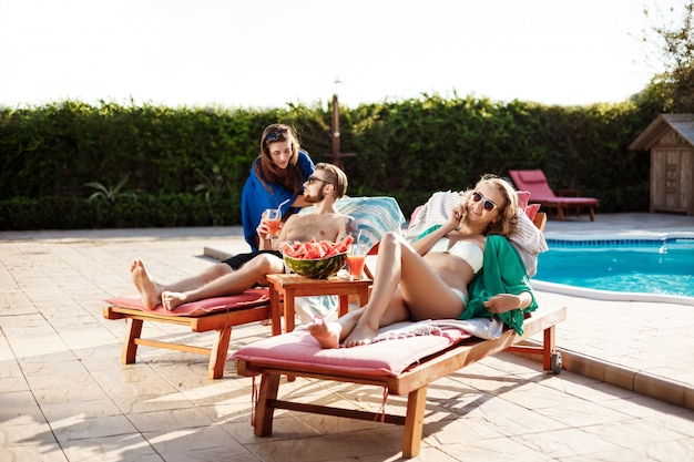 Friends smiling, speaking, sunbathing, lying on chaises near swimming pool