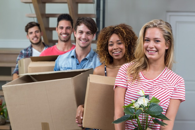 Friends smiling while carrying boxes in new house