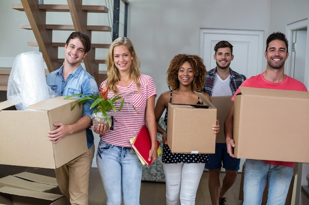 Friends smiling while carrying carton in new house