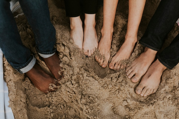Friends soaking their feet in the sand