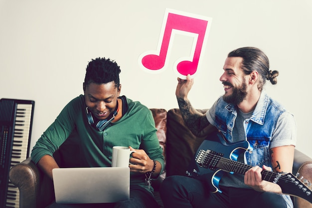 Friends in a songwriting process holding a musical note