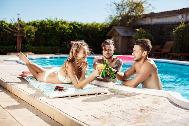 友達のスピーキング、笑顔、カクテルを飲み、休憩、スイミングプールのそばでリラックス