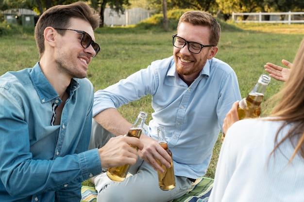 屋外で一緒に時間を過ごし、ビールを飲んでいる友達