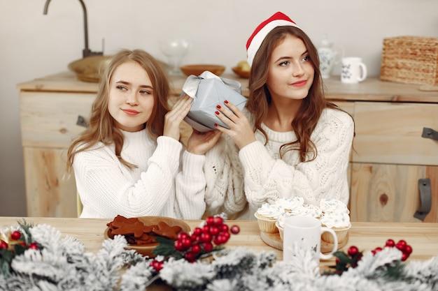 友達は家で時間を過ごしました。二人の女の子がお茶を飲みます。サンタの帽子をかぶった女性。
