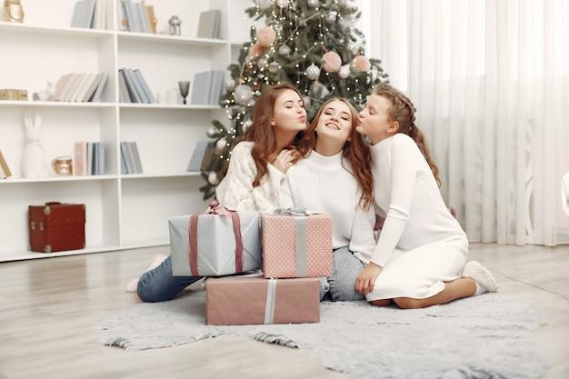 Друзья проводили время дома. две девушки с рождественским подарком. сестры вместе.