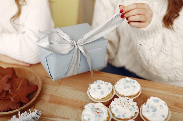 Друзья проводили время дома. две девушки с рождественским подарком. женщина в новогодней шапке.