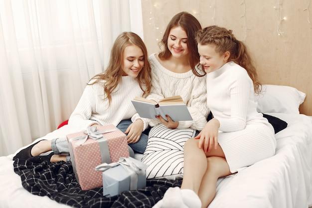 友達は家で時間を過ごしました。贈り物を持つ女性。本を持った姉妹。