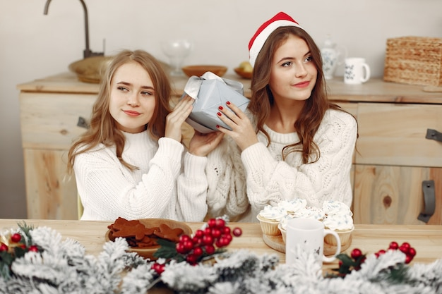 Friends spent time at home. two girls drink tea. woman in a santa's hat.