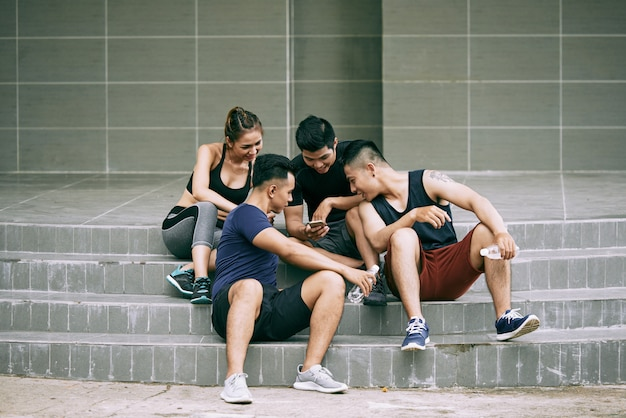 Friends in sportswear taking a break from jogging seated on stairs and watching videos on smartphone