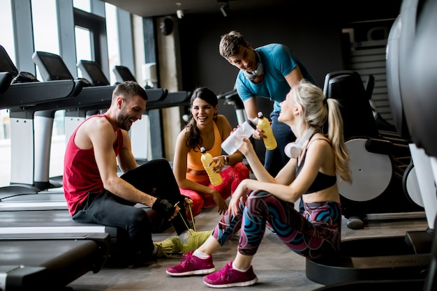 Friends in sportswear talking and laughing together while sitting on the floor of a gym after a workout