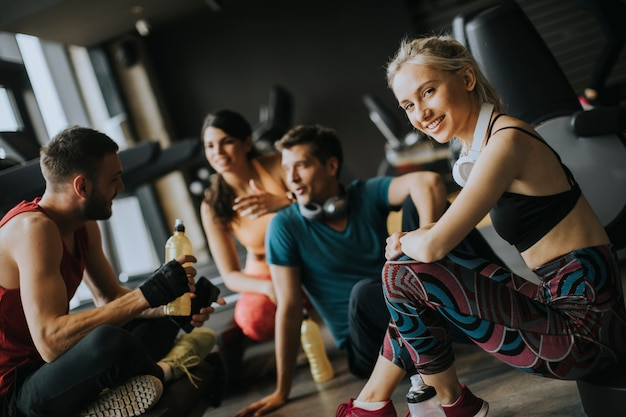 Friends in sportswear talking  together while standing in a gym after a workout