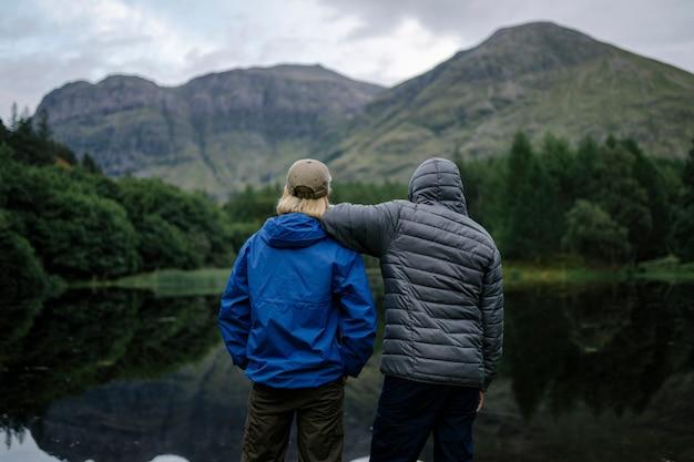 高地の川岸に立っている友人