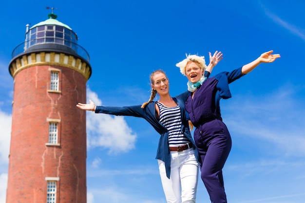 Friends standing at lighthouse on ocean