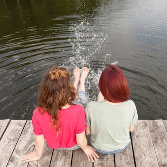 Friends staying on dock and splashing water with their feet+