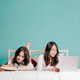 Friends studying on bed