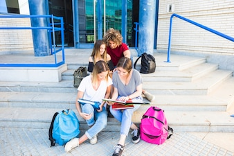 Friends studying on steps of university building