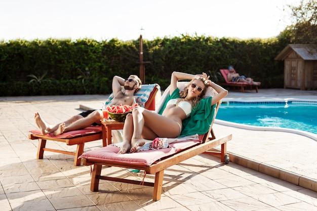 Friends sunbathing, lying on chaises near swimming pool