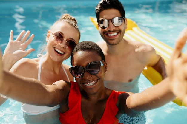 Friends in sunglasses pose on camera in the pool