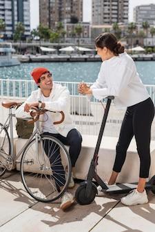 자전거와 스쿠터를 탄 후 휴식을 취하는 친구