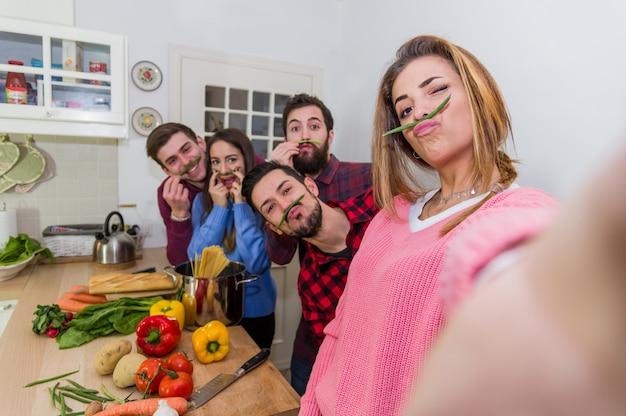 テーブルいっぱいの野菜とパスタの前に立っている間、緑色の豆の茎を鼻の下に身に着けているキッチンで自撮りをしている友人