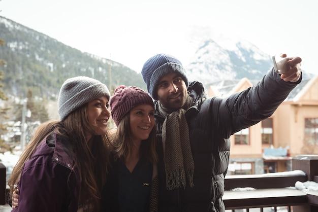 携帯電話を使って自分撮りをしている友達