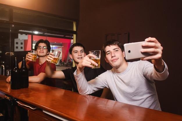 Друзья делают селфи, попивая пиво в баре.