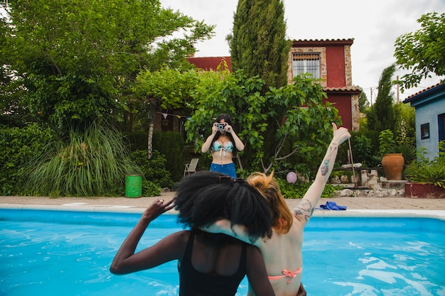 Friends taking pictures in the pool