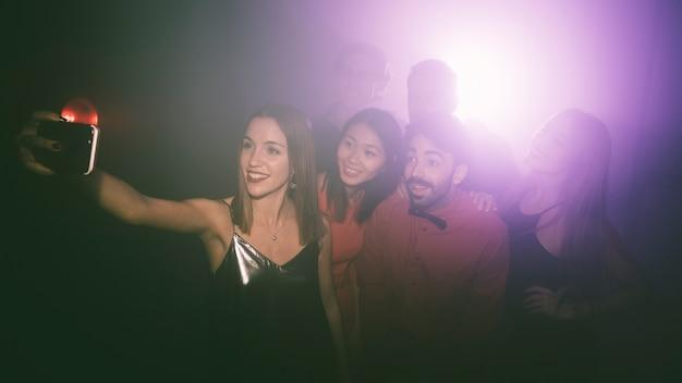 Friends taking selfie in club