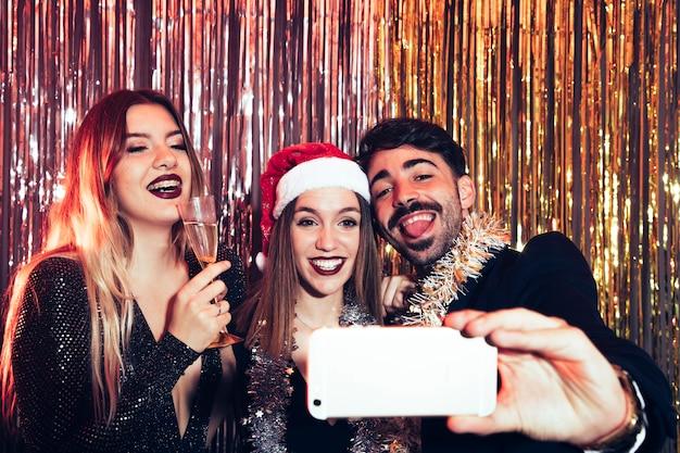 Amici che prendono selfie su partiti di nuovi anni