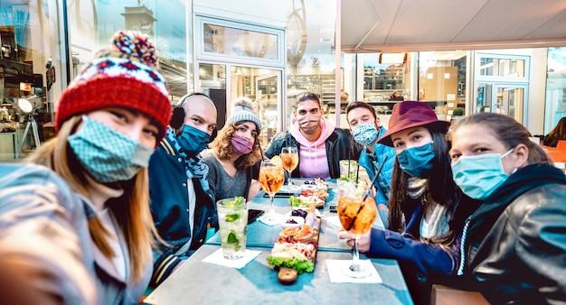 カクテルバーで外で自分撮りをしている友達-フレームの中央部分に選択的に焦点を当てる