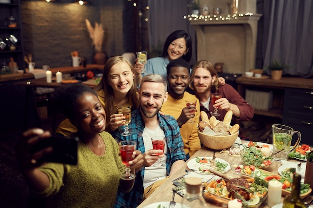Friends taking selfie photo at dinner party