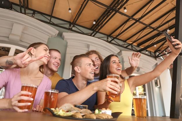 Друзья, делающие селфи, попивая свежее пиво в пабе