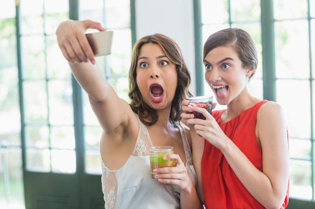 Friends taking a selfie while holding cocktail glasses