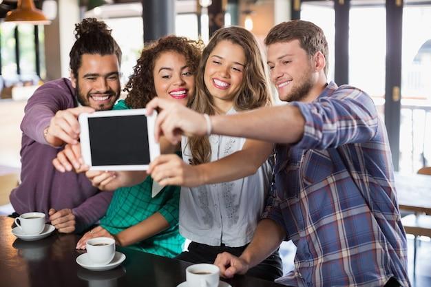 Друзья, делающие селфи с цифровым планшетом в ресторане