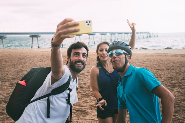 サイクリングウェアを着たビーチでスマートフォンで自分撮りをしている友達