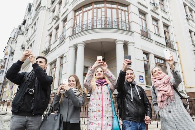 Друзья делают снимки с гаджетами на улице Бесплатные Фотографии