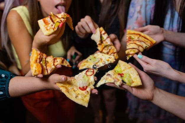 プレートからおいしいピザのスライスを取っている友人は、ビューを閉じます。