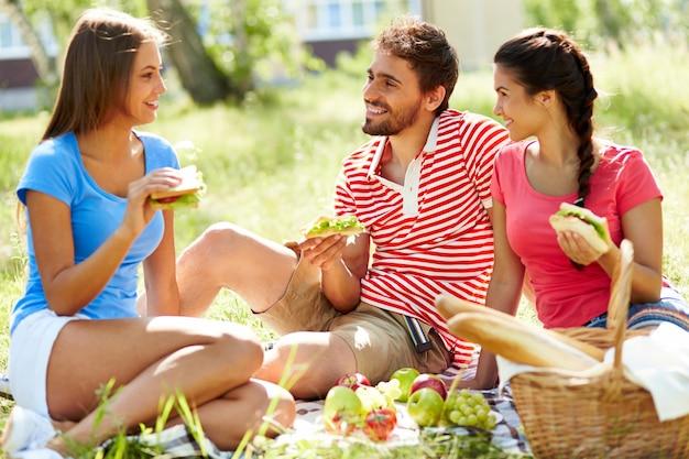 Amici a parlare e mangiare nel parco
