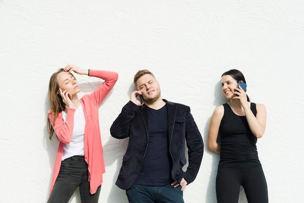 Друзья разговаривают по мобильному телефону на белом фоне