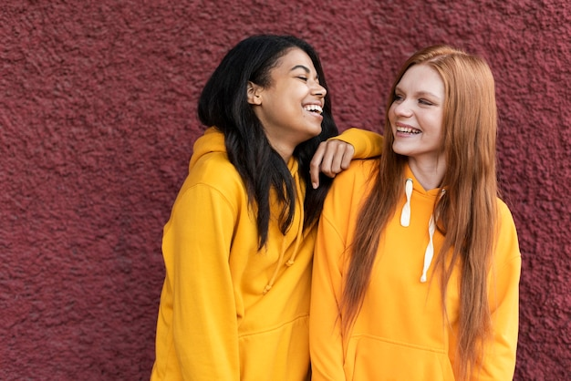 Friends talking while wearing yellow hoodies