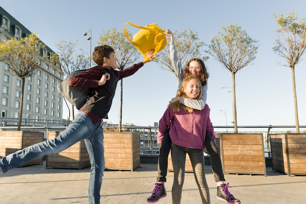 学校から行く途中で楽しんでいる学校のバックパックを持つ10代の学生の友達