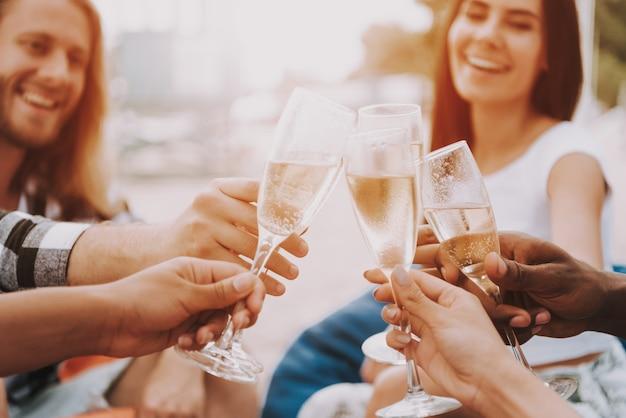 Friends toasting on beach glasses in sun light