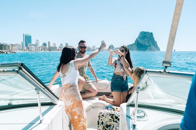 ボートパーティーで飲み物を乾杯する友達