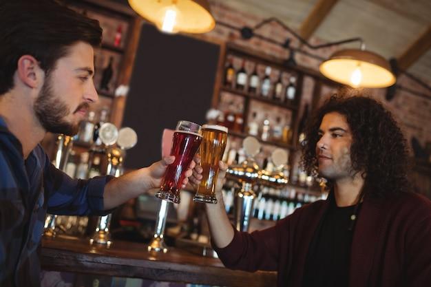 友達のバーカウンターでビールのグラスを乾杯