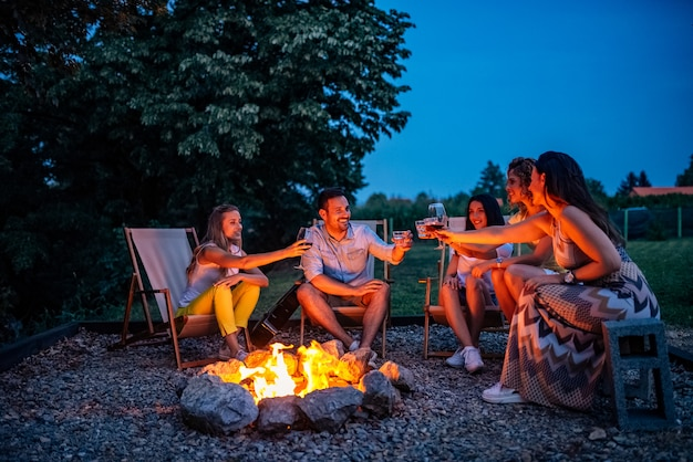 Friends toasting while sitting around fire pit.