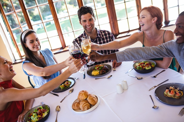 Friends toasting wine glass at table in restaurant