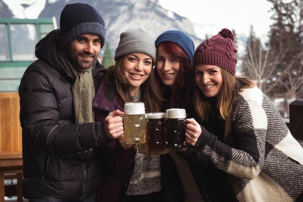 Amici che tostano con bicchieri di birra al bar