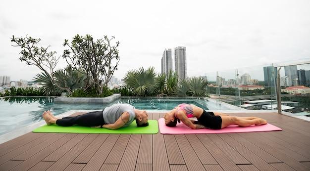 Друзья вместе на открытом воздухе практикуют позы йоги у бассейна
